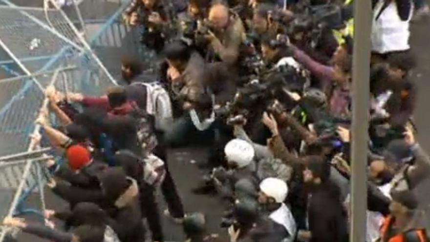 Momento en que un grupo de jóvenes encapuchados fuerza la valla y lanza objetos en el 25A. Inmediatamente después sucedió la carga policial (Captura del streaming de Live!)