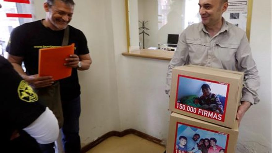 El representante de Bomberos en Acción Jorge Landete (i) entrega a un funcionario de la Secretaría General de Inmigración e Emigración más de 150.000 firmas para pedir al Gobierno que traslade a España con la mayor urgencia posible a Osman. | EFE