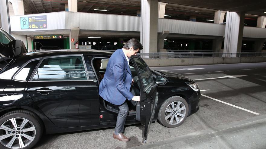 El exministro Soria se sube a un coche policial camuflado a su llegada al aeropuerto de Gran Canaria este viernes. (ALEJANDRO RAMOS)