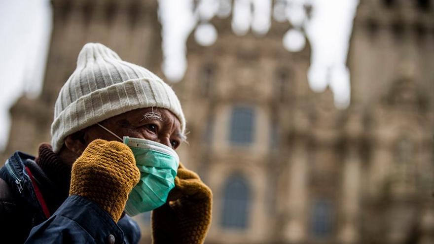 Un turista se coloca una mascarilla en la plaza del Obradoiro antes de decretarse el estado de alarma.
