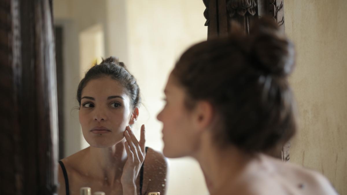 Una mujer se mira al espejo.