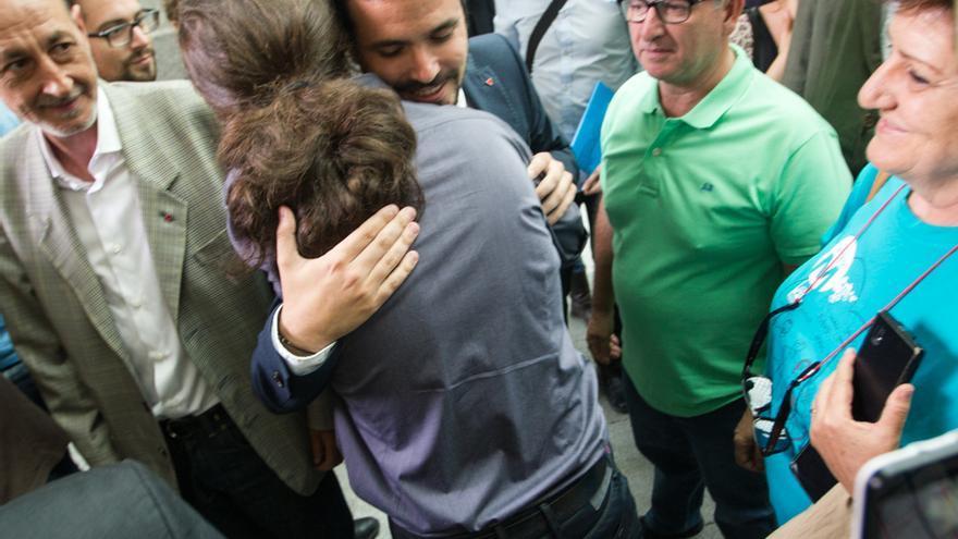 Pablo Iglesias (de espaldas) y Alberto Garzón se saludan durante la toma de posesión de Manuela Carmena. / Mariano Neyra