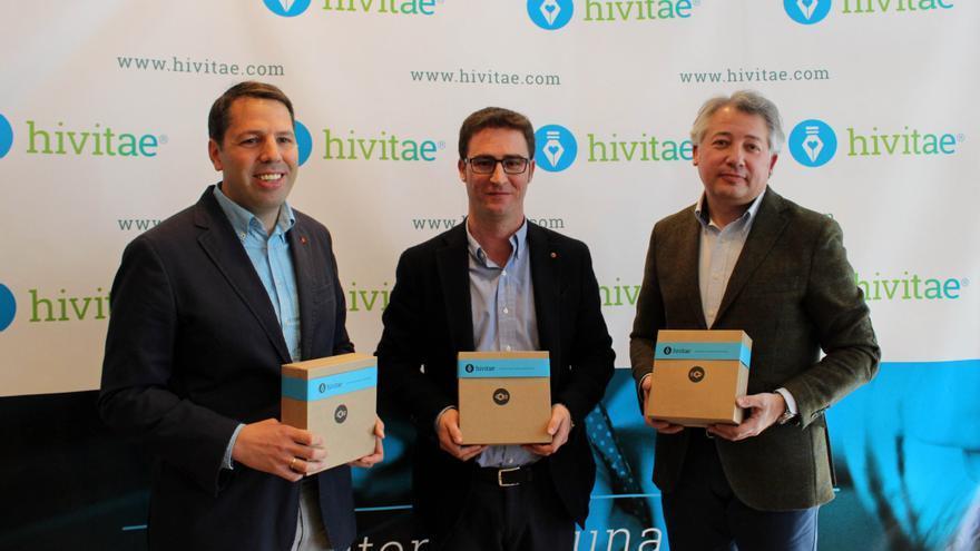 Los responsables de la empresa Hivitae sostienen una caja con un libro, tal como llegará al usuario que lo demande.