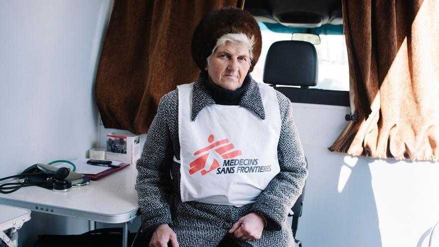 Una de las voluntarias de MSF posa en el interior de una clínica móvil, en Mayorsk, Ucrania. MSF ha establecido puntos de primeros auxilios y suministro de agua para ayudar a la población que debía esperar largas colas, en condiciones meteorológicas extremas (por frío o calor), para cruzar la línea del frente en los puestos de control de Artemovsk-Gorlovka, Volnavakha-Donetsk y Mayorsk. © Christopher Nunn/MSF