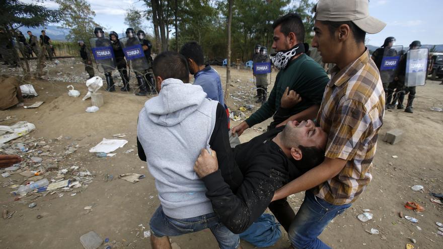 Tres hombres trasladan a un herido en los enfrentamientos con la policía macedonia al intentar cruzar la frontera griega. / Darko Vojinovic - AP
