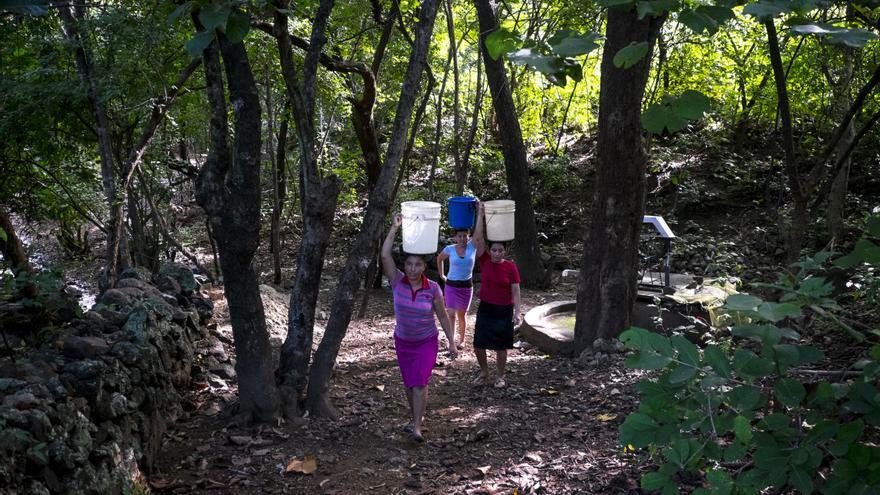 Tres mujeres sin agua en sus hogares soportan sobre sus cabezas el peso de bidones para llevarlo hasta sus casas./ Pedro Armestre.