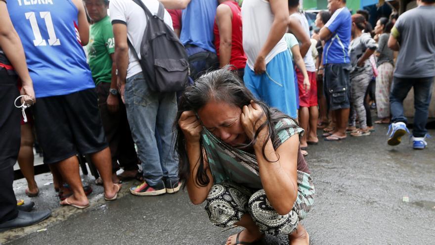Una mujer llora, mientras el resto mira el cadáver de una mujer asesinada por dos hombres sin identificar cuando llevaba a sus hijos a la escuela. 8 diciembre 2016. © APPhoto/Bullit Márquez