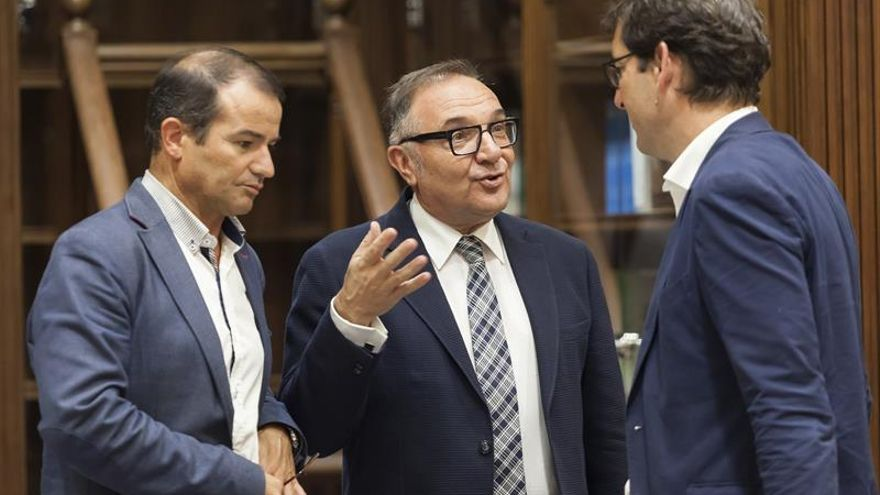 El consejero de Sanidad del Gobierno de Canarias, José Manuel Baltar (c), conversa con los diputados del Grupo Socialista en el Parlamento de Canarias, Lavandera (d) y Hernández (i)
