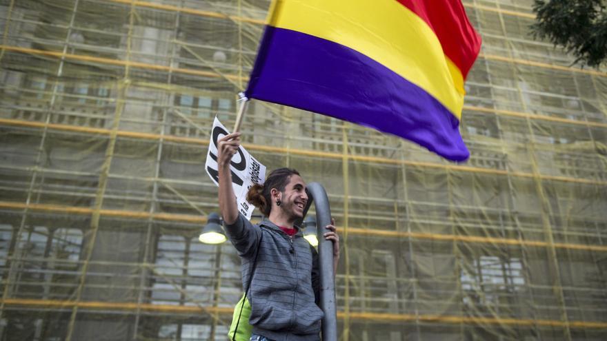 """Un joven manifestante ondea una bandera republicana frente al edificio del Banco de España, durante la manifestación """"rodea el Congreso"""""""