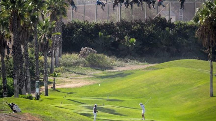Valla de Melilla con doce personas doce inmigrantes frente a campo de golf. Fotografía José Palazón-Pr
