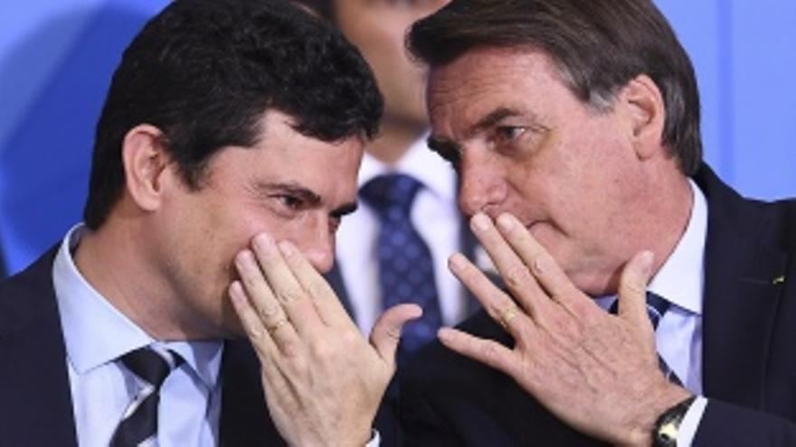 """El presidente Jair Bolsonaro cuchicheando con su entonces ministro de Justicia, el ex juez Sérgio Moro, primer coordinador del """"grupo de tarefas"""" Lava Jato"""