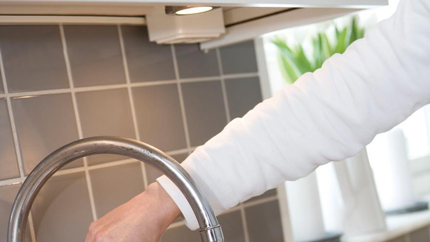 Una persona toma agua de un grifo