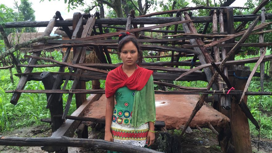 """Kamala posa al lado de su """"goth"""", la cabaña en la selva donde duerme los días que tiene la menstruación © WaterAid/ Cecile Shrestha"""