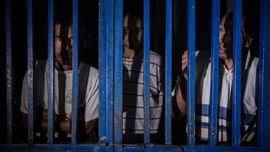 Tres pacientes mirando a través de una reja metálica hacia el exterior de su habitación en el Hospital Psiquiátrico de Caracas ubicado en Lídice, Caracas (Venezuela).