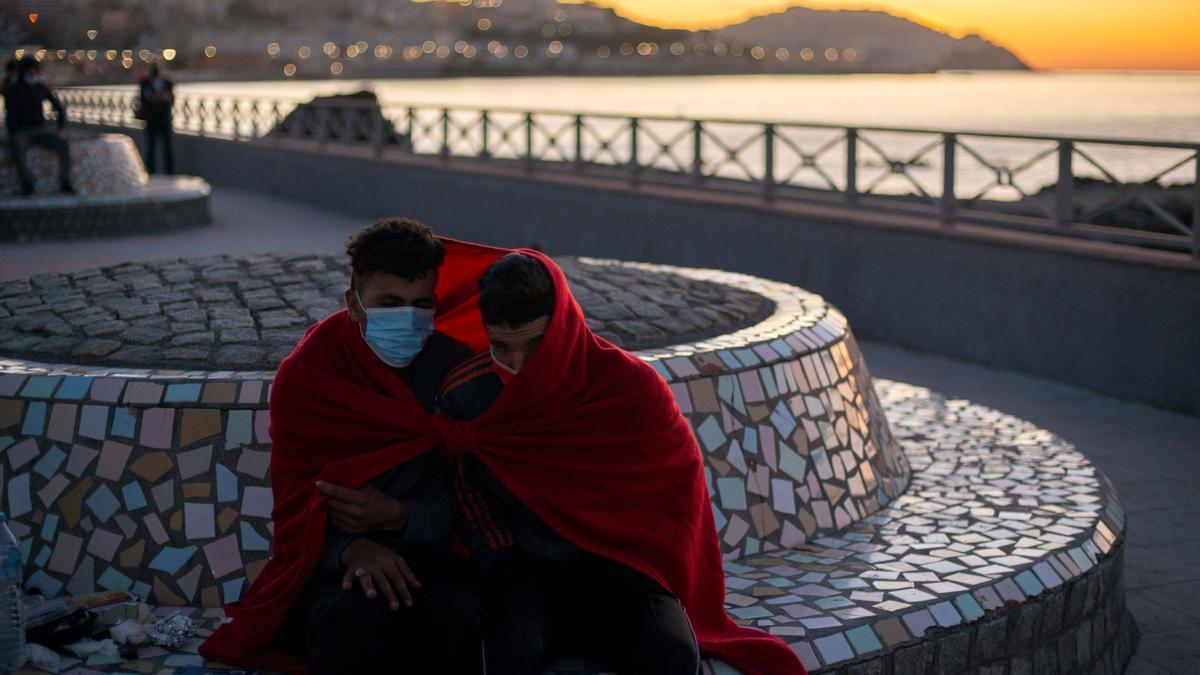 Dos jóvenes migrantes se protegen del frío a primera hora de la mañana de este miércoles cerca de la playa ceutí de El Tarajal.