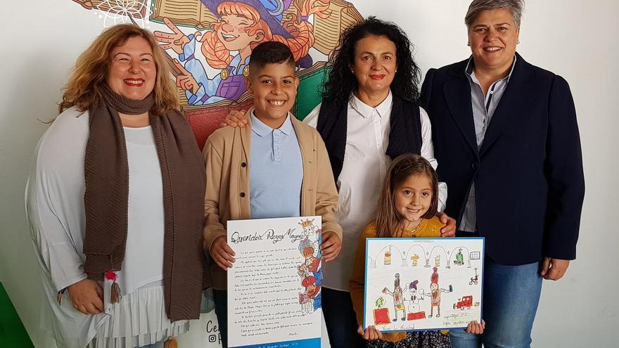 Leire Martín y Alberto Fernández, ganadeores el concurso escolar de tarjetas navideñas y cartas a los Reyes Magos convocado por el Ayuntamiento de Los Llanos, con la alcaldesa, Noelia García (d), y la concejal  de Cultura, Charo Palmero (i).