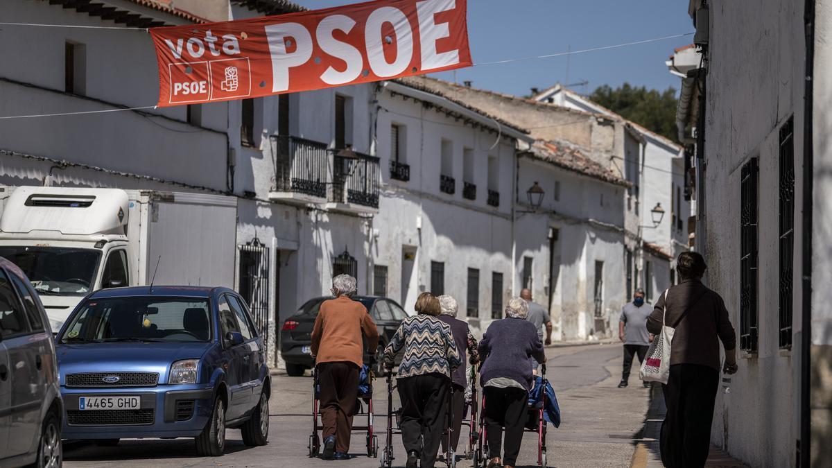 Vecinos de Fuentidueña, en una de las calles del pueblo, todavía con propaganda electoral.