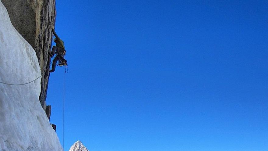 En el segundo largo de la vía 'Standhart' inmersos en una situación típica en Patagonia: una zona desplomada de 5.10, con las  botas y los crampones colgando del arnés, y con un espectacular escenario de fondo (© Facebook de Colin Halley).