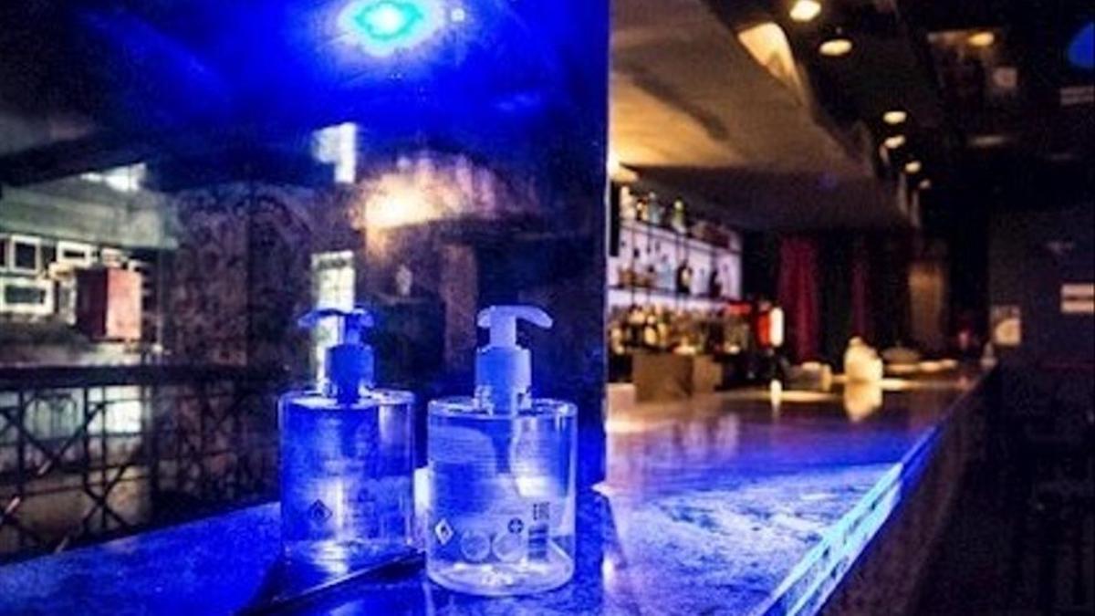 Interior de una discoteca con gel hidroalcohólico en la barra.