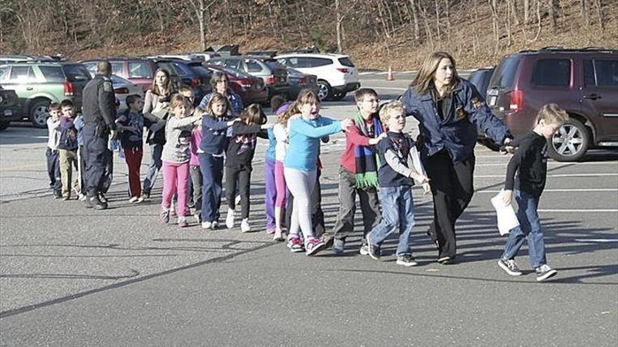 Fotografía cedida que muestra a unos agentes de Policía evacuando a unos niños de la escuela Sandy Hook en Newtown (Connecticut, EE.UU.) después de registrarse un tiroteo en el centro escolar. EFE/Newton Bee