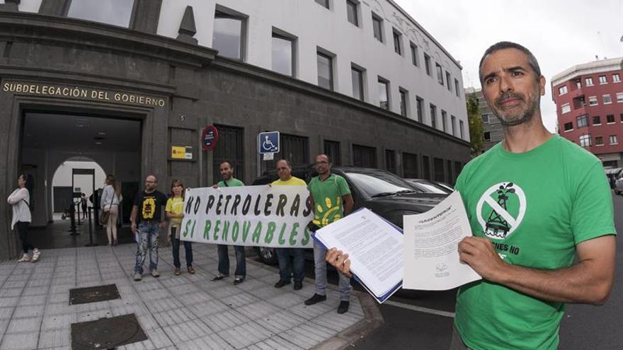 El portavoz de Greenpeace, Julio Barea, muestra el informe negativo, antes de entregarlo en el registro de la Delegación del Gobierno en Canarias. EFE/Ángel Medina G.