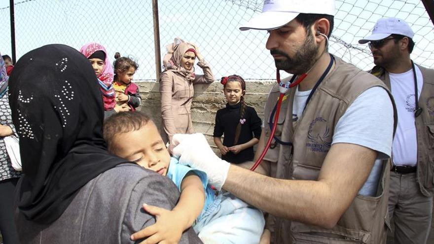 Voluntarios de la Organización No Gubernamental 'Doctores de Chipre' atienden a un niño en el campo de refugiados instalado en la isla de Chios, Grecia. EFE/Archivo