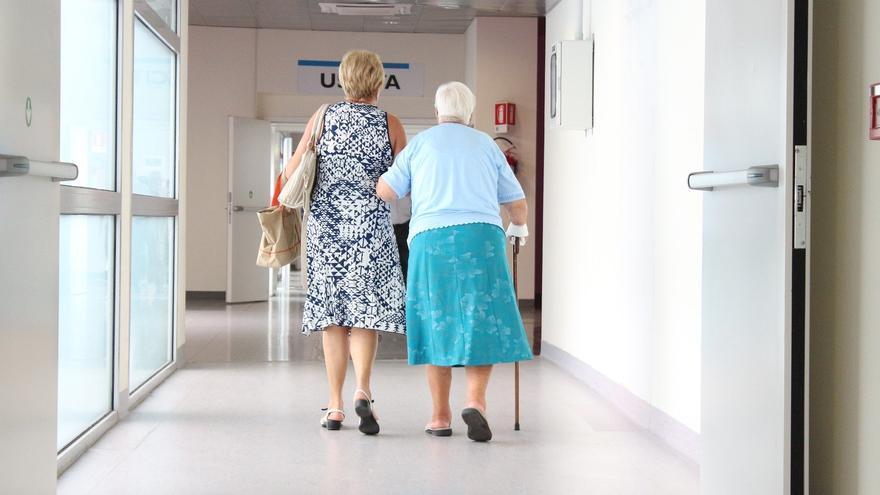 Cuidadora junto a una persona mayor en hospital.