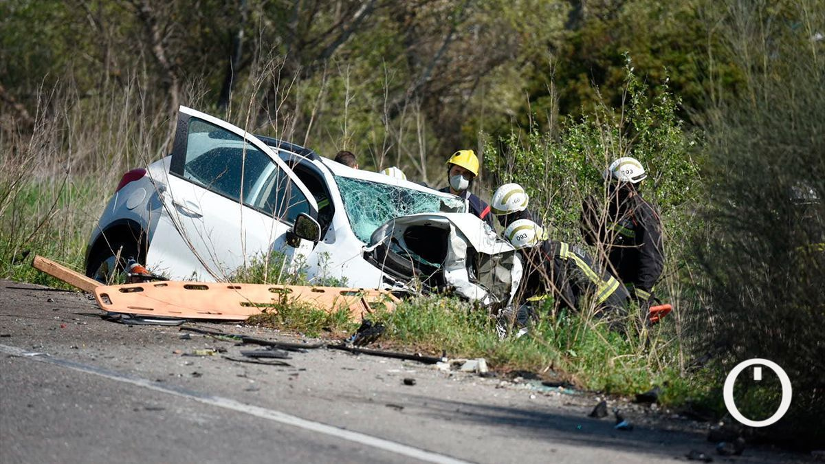 Los bomberos junto a uno de los vehículos del accidente de tráfico en la antigua nacional N-IV este sábado.