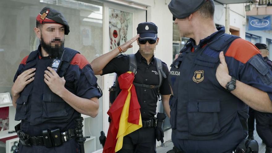 Un policía con una bandera española hace el saludo a dos mossos tras salir de un hotel de Pineda del Mar el 5 de octubre de 2017.