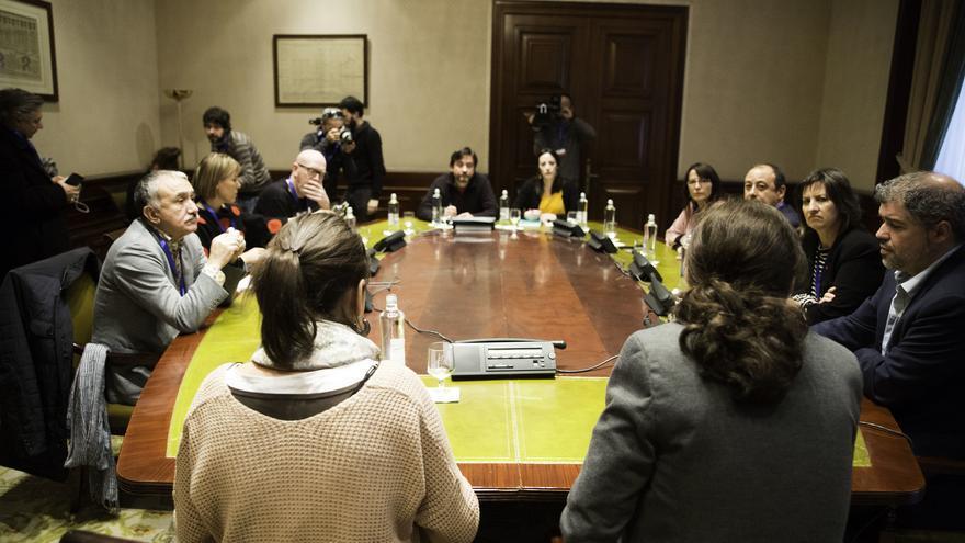 Pablo Iglesias, de espaldas, durante una reunión en el Congreso con los líderes de CCOO, Unai Sordo, y UGT, Pepe Álvarez, en 2017.