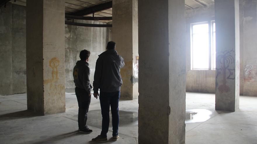 La planta inferior del edificio levantado por Negrín encima de la Mina. A la izquierda, el bombero Ferran Riera y a la derecha, el alcalde de la Vajol Joaquim Morillo. En el techo se conserva una parte de los raíles que se usaban para mover la carga.