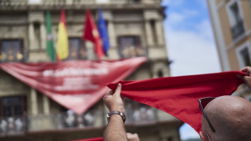 Archivo - Un hombre alza un pañuelo rojo en las inmediaciones de la Plaza del Consistorio en el momento en el que de celebrarse los Sanfermines 2020.