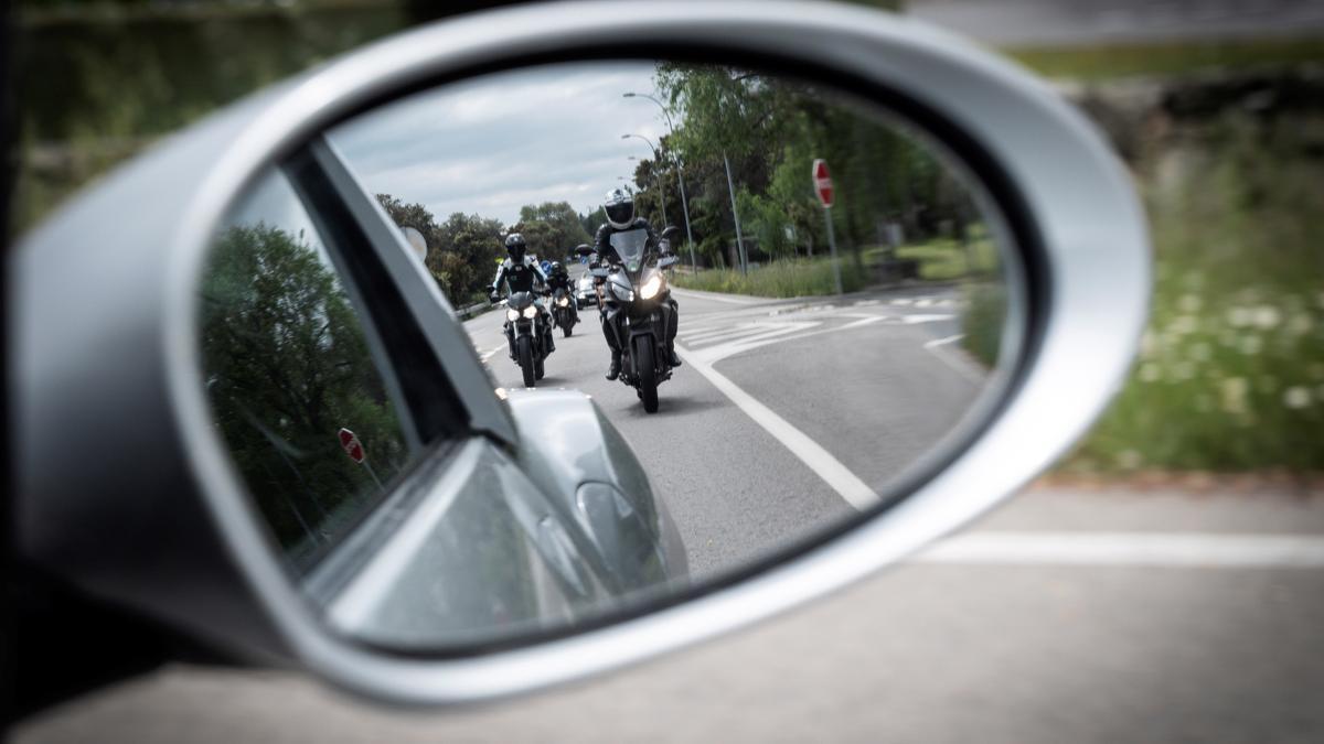 Motoristas aparecen reflejados en el retrovisor de un coche.