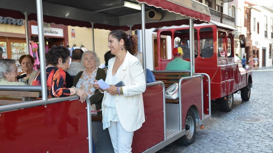 La consejera de Asuntos Sociales del Cabildo, Jovita Monterrey Yanes, con algunas pasajeras del tren, en la Calle Real.
