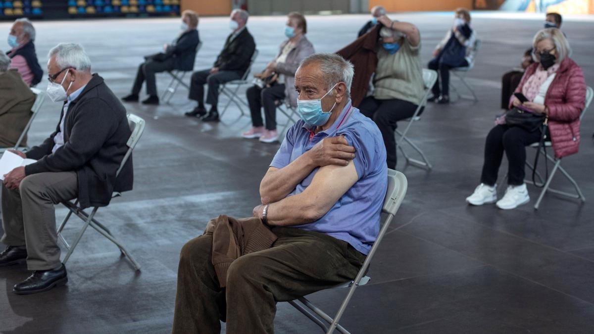 Varias personas tras recibir la vacuna de Pfizer en el recinto ferial Expourense en Orense.