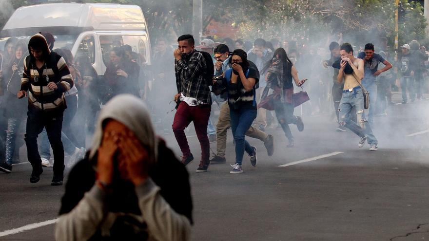 Manifestantes antitaurinos huyen del gas lacrimógeno y gas pimienta lanzado por la policía en los disturbios del pasado domingo en las proximidades de la plaza de Bogotá.