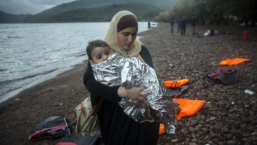 Una mujer coge a su bebé después de llegar de la costa turca a la localidad de Skala Sikaminias, en el noreste de la isla griega de Lesbos. | Santi Palacios - AP