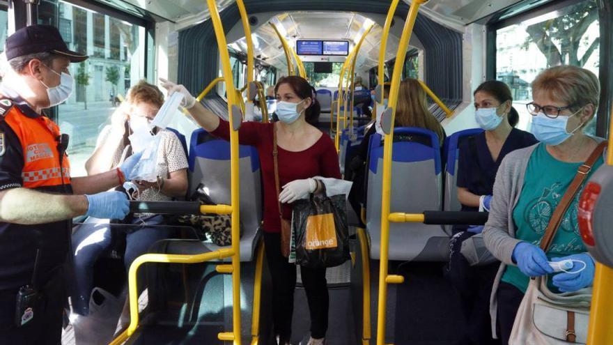 Miembros de protección civil entregan mascarillas a los pasajeros de autobuses.