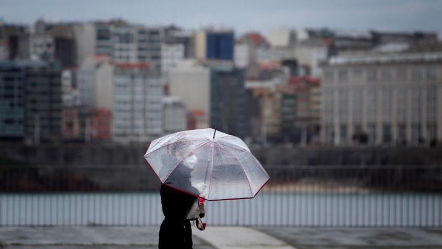 Una mujer camina por el paseo marítimo de A Coruña, cubierta con paraguas y mascarilla.