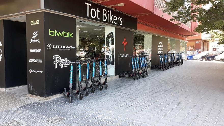 Varios patinetes de MOVO estacionados en una acera de València