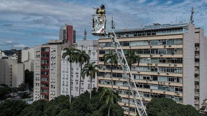 Un bombero fue registrado este miércoles al dar un concierto a 50 metros de altura, para animar a los cientos de habitantes de un barrio en Río de Janeiro (Brasil).