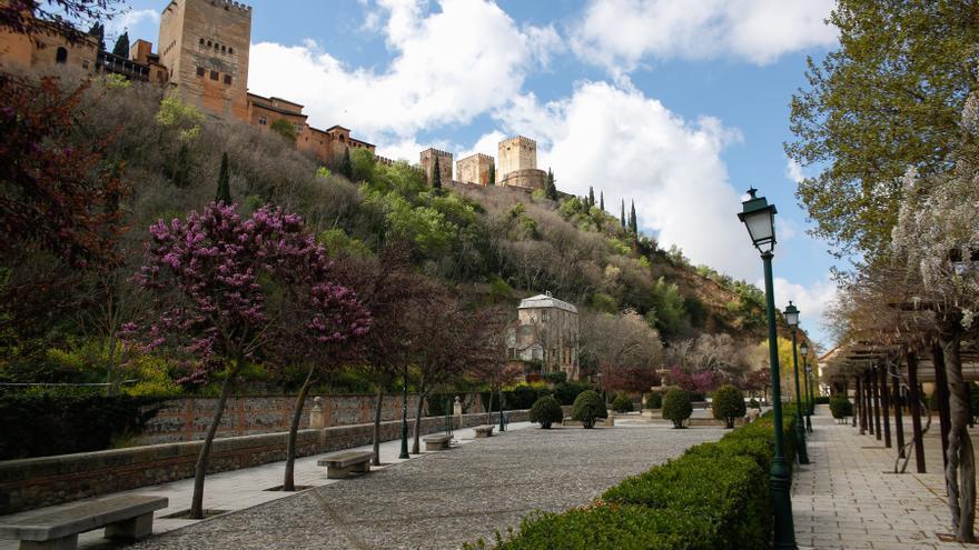 El paseo de los tristes de Granada desierto con la Alhambra, también vacía, al fondo