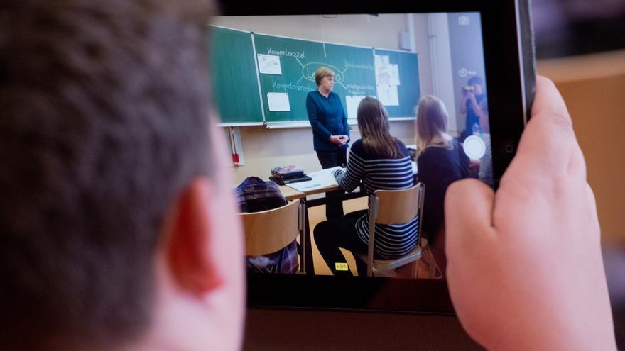 Un estudiante graba la imagen de la canciller Angela Merkel, de visita en una escuela de Berlín.