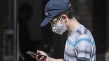 Un joven con mascarilla mira su teléfono móvil.