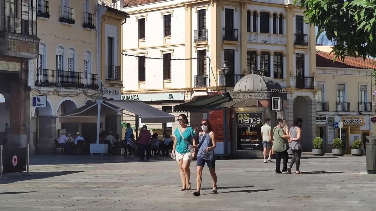 Varias personas, con y sin mascarilla, pasean por la plaza de España de Mérida