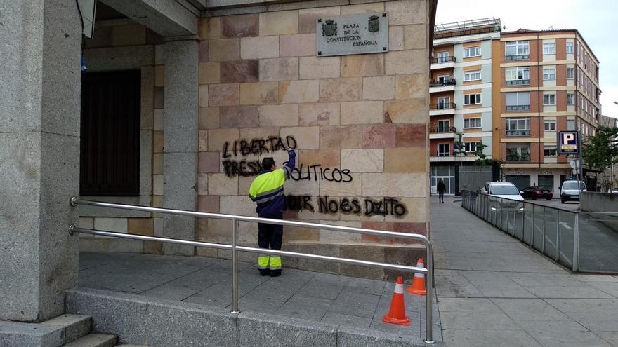 Un operario limpia las pintadas en el exterior del edificio de la Subdelegación del Gobierno en Zamora.