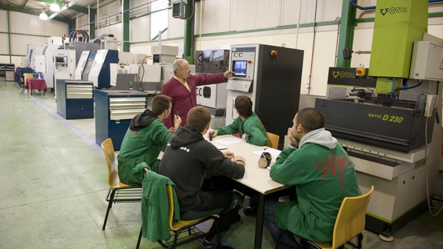Un profesor explica a unos alumnos de formación profesional el funcionamiento de una máquina.