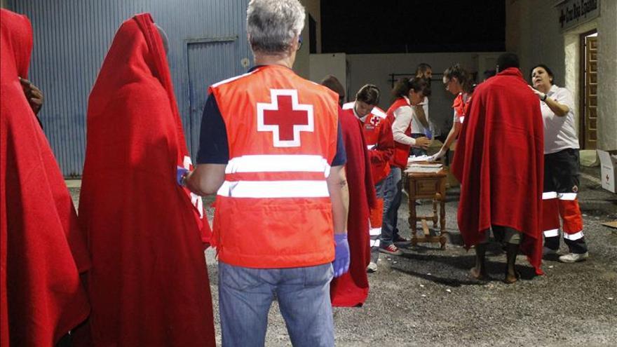 Miembros de la Cruz Roja atienden a las personas que llegaron esta noche al puerto de Motril, en Granada./ Efe.