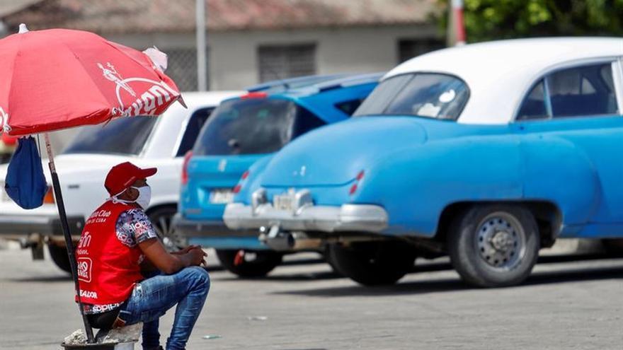 Un hombre que se dedica a cuidar y parquear vehículos descansa bajo la sombra de un paraguas en una azotea de un barrio en La Habana, (Cuba).
