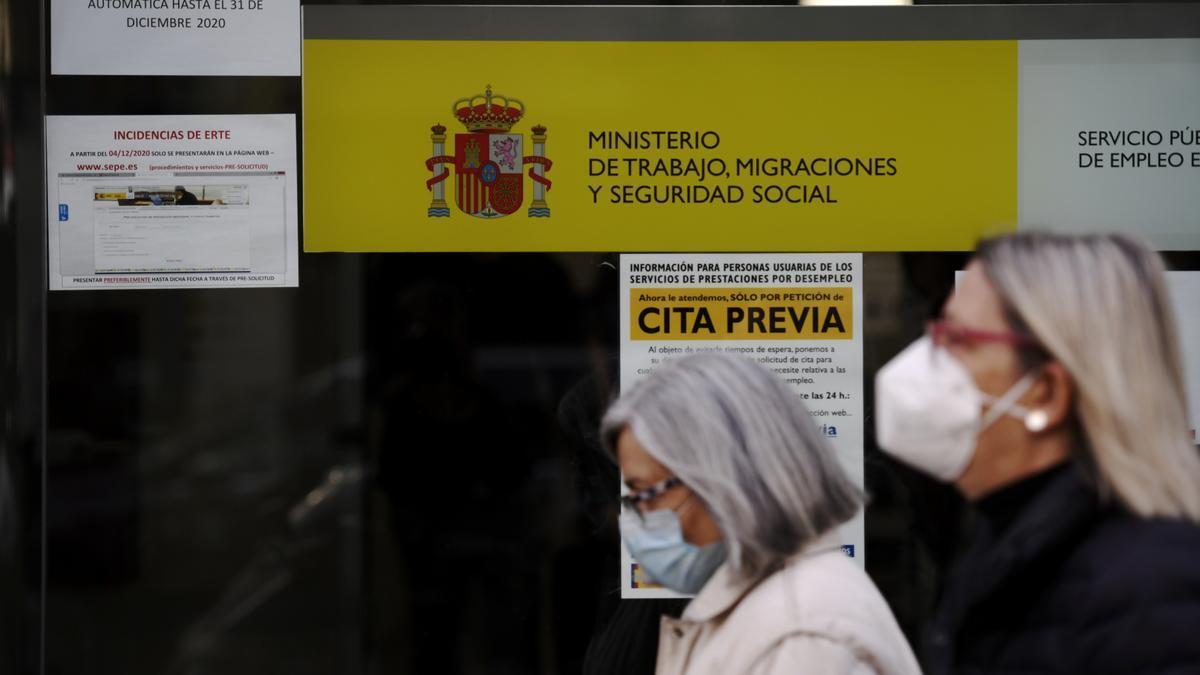Dos mujeres pasan por la puerta de una oficina de empleo, SEPE (antiguo INEM) horas después de conocer los datos del paro de noviembre, en Madrid (España), a 2 de diciembre de 2020.